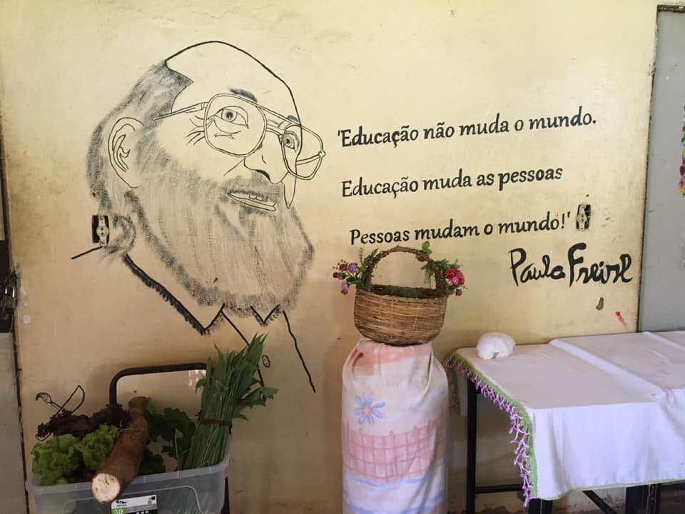 """Photo above: Table, basket, plants at MST school in Brasil in front of a mural of Paulo Freire and his quote (translated), """"Education does not change the world. Education changes people. People transform the world."""""""